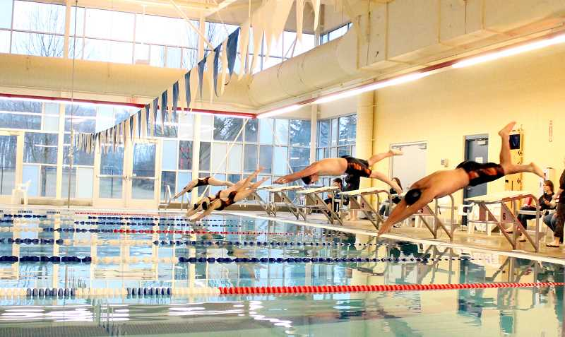 by: CORY MIMMS - Members of Molalla's swim team dive in at the Molalla Aquatic Center during the first home meet.