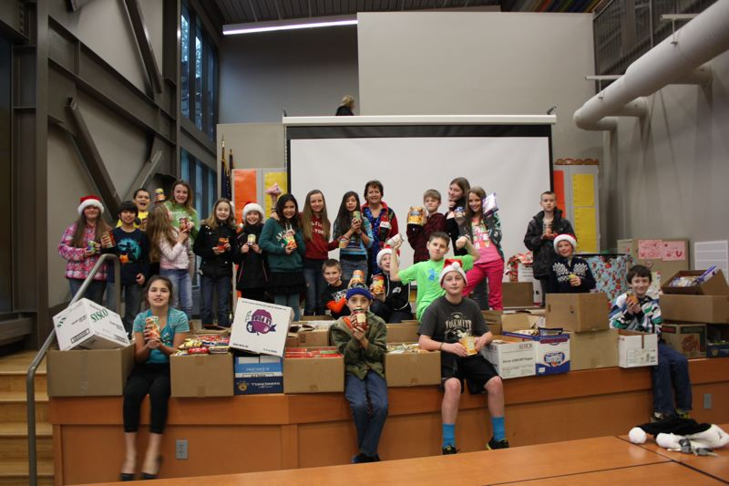 by: SPOTLIGHT PHOTO: ROBIN JOHNSON - Ronda Kienlen's fifth grade class at Otto Peterson Elementary School raised the most overall items of any class for the school's holiday food drive which ended Friday, Dec. 20. Kienlen's students brought in 765 total items during the drive. As a whole, the school brought in a total of 3,353 items which will be donated to the Scappoose Rural Fire District's Share and Care Food Drive.