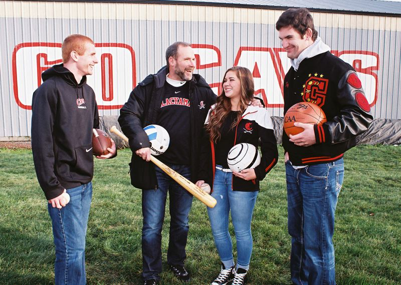 by: JOHN DENNY - Clackamas athletic director Jeff Erdman shares memories with multi-sport senior athletes Cade Wilkins (left) and Taylor Stinson (right), and his daughter Shelby, as he prepares to step down after 14 seasons as Clackamas High School athletic director.