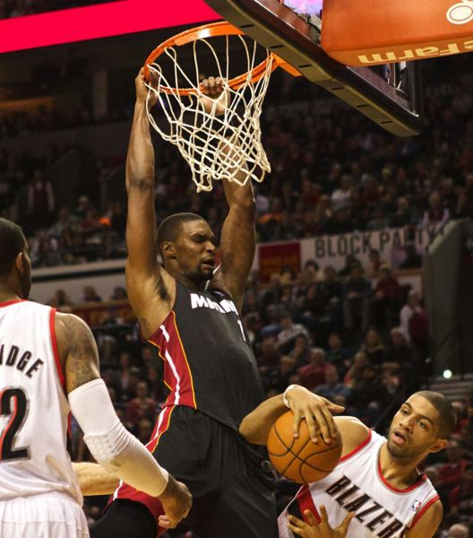 by: TRIBUNE PHOTO: JAIME VALDEZ - Miami's Chris Bosh dunks over Nicolas Batum (right) en route to his 37 points.