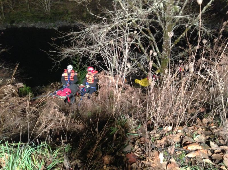 by: CLACKAMAS COUNTY SHERIFF'S OFFICE - Emergency services crews pull one of the two occupants of a vehicle that crashed into the Mollala river early Sunday morning.