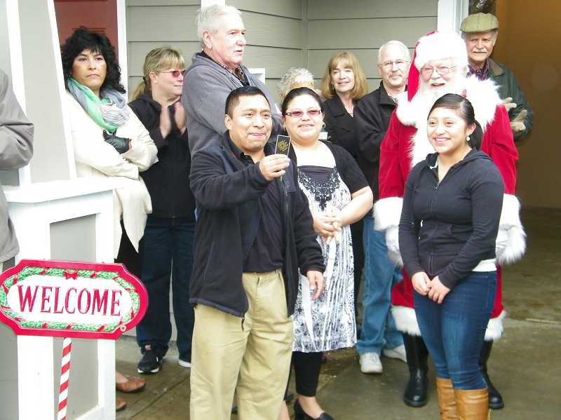 by: COURTESY PHOTO: WEST TUALITY HABITAT FOR HUMANITY - Jose Quim holds the key to his new Forest Grove home as his wife, Silvia Sop, and daughter Ada are all smiles just behind him. Santa delivered the key and hung around for the photo Saturday, Dec. 21.