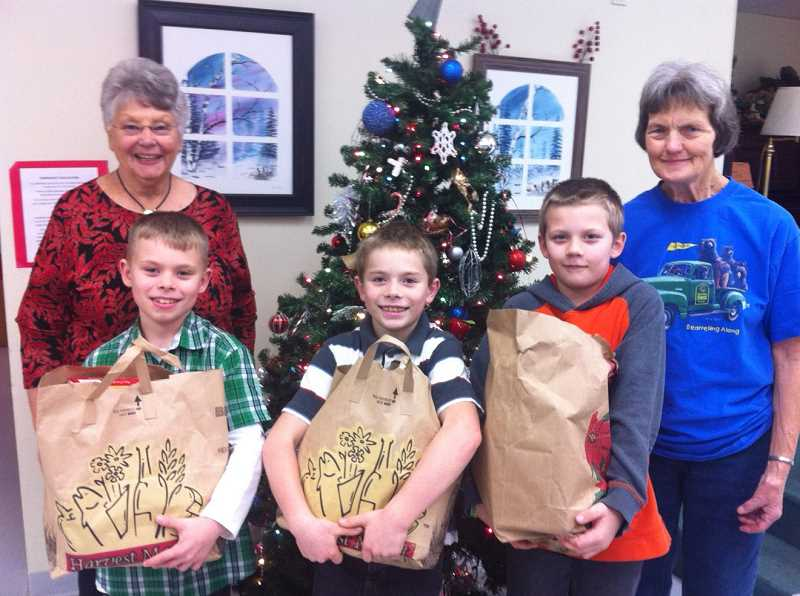 by: CONTRIBUTED PHOTO: TERRA EMERSON - Peggy Richards and Jan Melcher of the Estacada Community Center are all smiles as they pose with three Clackamas River Elementary students who celebrated their birthdays by collecting food to donate to the community center.  From left, fourth-grader Carson Emerson, third-grader Cory James and fourth-grader Jacob Sittner hold up heavy bags of donated food.