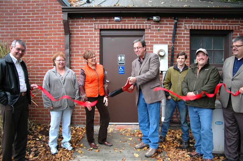 by:  ISABEL GAUTSCHI - Mayor Brent Dodrill cuts the ribbon for the new public restroom in the City Hall building. (From left) City Manager Bill Elliott, Dana Heston (representing Steve Locke Construction), Jae Heidenreich of the Clackamas County Tourism and Cultural Affairs Office, Estacada Chamber of Commerce President Jordan Winthrop and City Councilors Sean Drinkwine and Rob Gaskill gather for the ceremony.