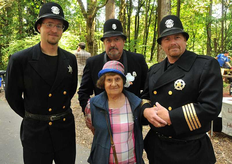 by: VERN UYETAKE - West Linn officers dressed up in old-fashioned uniforms for the citys centennial celebration in August at Mary S. Young State Park. During the event they came across West Linn resident (and big police booster) Alice Richmond and pretended to arrest her.