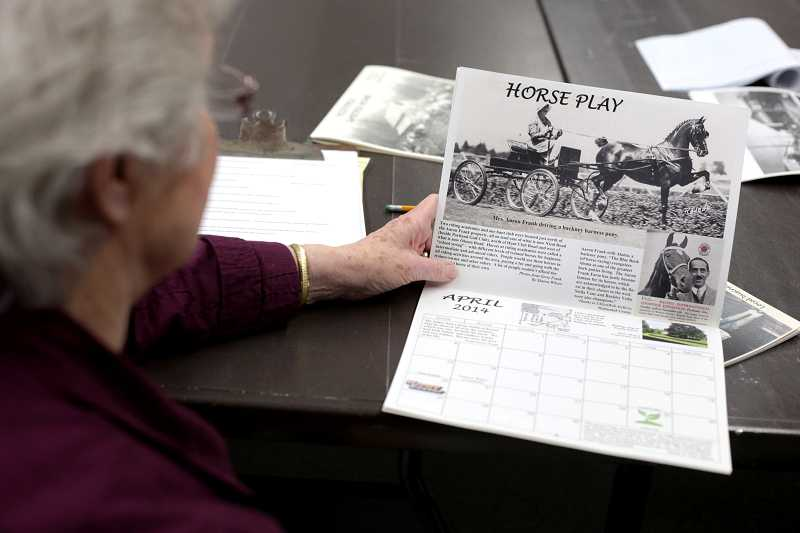 by: TIMES PHOTO: JONATHAN HOUSE - Elaine Shreve looks at the 2014 Garden Home Calendar, featuring historical photos.