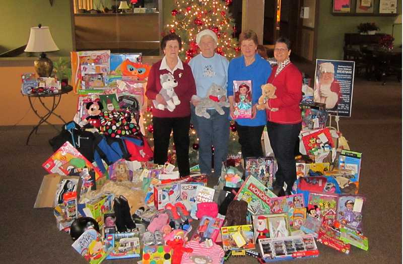 by: BARBARA SHERMAN - KATHY AND FRIENDS - Kathy Peper (second from right), who organized the Summerfield giving tree for Washington County foster children again this year, stands with all of the donated gifts and some of the friends who helped her with the project - Dee Melgreen (left), Yvonne Welch and Betty Benson.
