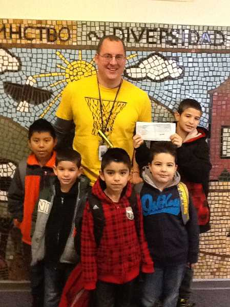 by: JUAN LARIOS - Glenn Hopkins, P.E. teacher at Washington Elementary School, is pictured with Washington students and a check for $350 from Maps Credit Union.