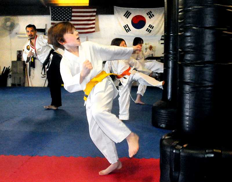 by: GARY ALLEN - Taking over -- Noah Staley practices kicks during the Taekwondo Kids Beginners class taught by Rhey Jauins at the Soaring Phoenix Family Martial Arts Academy. Soaring Phoenix opened last month replacing Dragonfly Martial Arts at 111 N. College St.