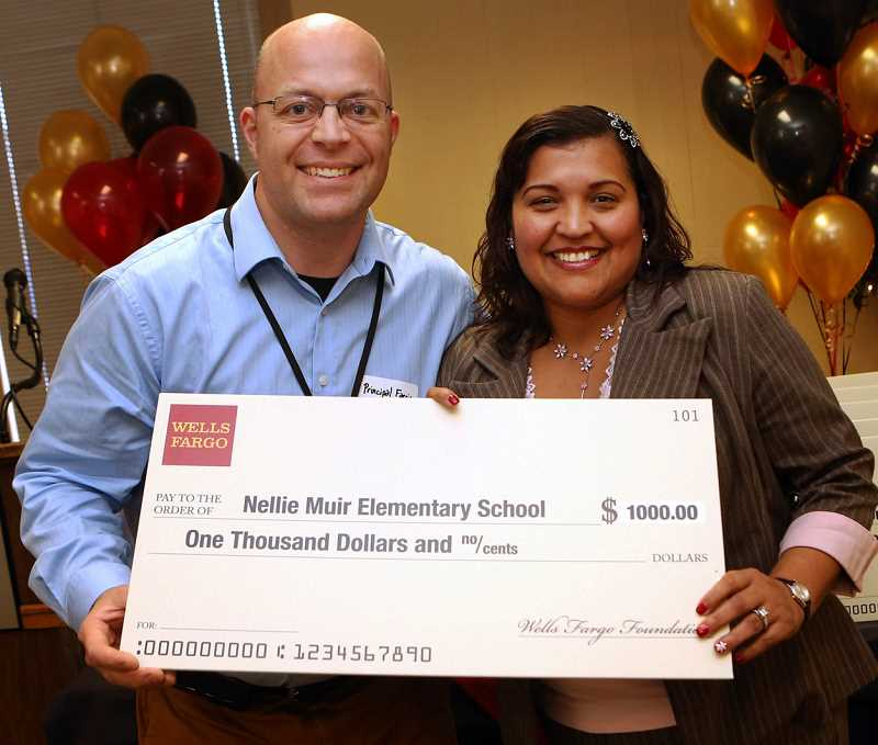 by: SUBMITTED - Nellie Muir Elementary Principal Todd Farris accepts a $1,000 grant check from Gabby Sanchez, manager of a Wells Fargo branch in Woodburn. Nellie Muir Elementary was one of 17 schools to receive a grant from the financial services company at an event Dec. 12 in Eugene.
