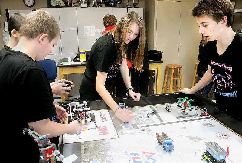 by: SETH GORDON - Tinkering around -- The C.S. Lewis Academy middle school robotics team, 'Unicorns of Fury,' makes adjustments to their robot during class before winter break. The team placed second at the district tournament to qualify for the FIRST LEGO League state championship Jan. 18-19 at Liberty High School.
