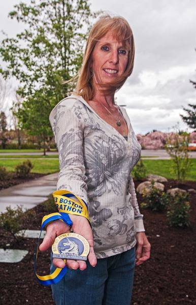 by: SPOKESMAN PHOTO: JOSH KULLA - City of Wilsonville employee Candi Garrett shows off her Boston Marathon finisher's medal.