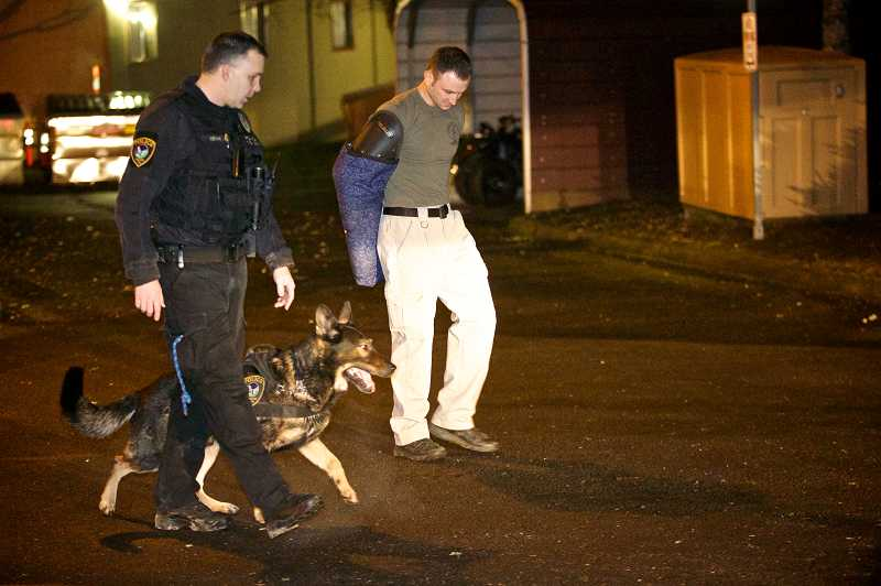 by: TIMES PHOTO: JAIME VALDEZ - Tigard Police officers Cameron Odam, left, and Mike Powers walk with Baxter during routine training.