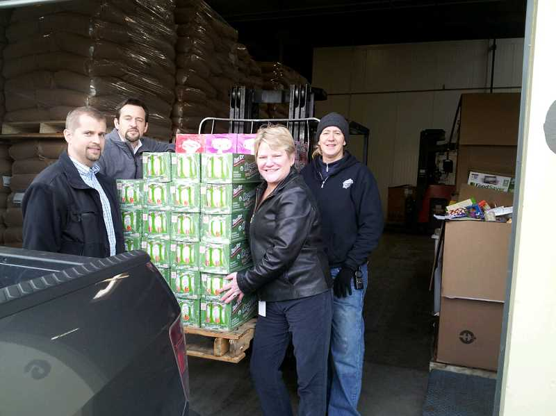 by: SUBMITTED PHOTO - Aequitas Capital staff traded their computers and office chairs for hardhats and pallet jacks as they unloaded more than 75 tons of food they collected for Oregon Food Bank. The donation - which equaled about three semi-trucks full - was the result of a month-long internal challenge. The staff of the Lake Oswego-based national financial services company prepared special packages for distribution for those in need throughout the Portland metropolitan area.