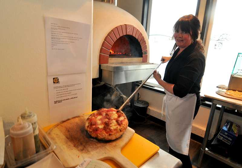 by: REVIEW, TIDINGS PHOTO: VERN UYETAKE - Lisa Shaw-Ryan pulls out a redhot pie from the giant oven at Chuckie Pies. She made a great guess that Lake Oswegans would come flocking to eat them.