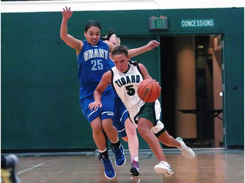 by: DAN BROOD - GREAT GUARD -- Tigard High School senior guard Lexi Carter (5), shown here driving past Grant's Justice West in the Tigers' first game of the season, will play college basketball at Clemson University.