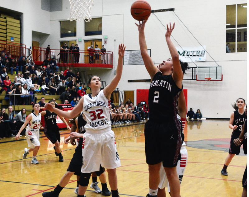 by: MATT SINGLEDECKER - UP FOR TWO -- Tualatin senior post Jasmine Miller (2) shoots over Westview senior Brittany Carlson in Friday's game. Miller led the Wolves with 20 points in the contest.