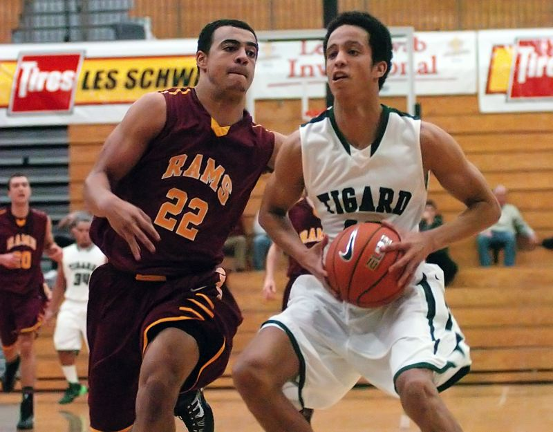 by: DAN BROOD - SIDE BY SIDE -- Tigard High School senior Elijah Simon (right) battles Central Catholic's Cameron Scarlett during Friday's first round game at the Les Schwab Invitational, held at Liberty High School. Simon scored 14 points to help the Tigers get a 64-53 win.