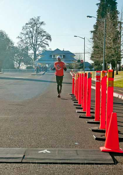 by: COURTESY PHOTO: GWENDOLYN HULLINGER PHOTOGRAPHY - A lone runner makes his way to the finish line at Tom McCall Upper Elementary School in Forest Grove at Saturdays Y2K14 Run, which raised money for the local Meals on Wheels program (above). Though temperatures hovered around freezing at the start of the annual New Years weekend event, many runners opted for bare legs (left). Race director Barb Schimmel said 520 people finished the 10K distance and 117 finished the 20.14K race. See page A2 for additional photos.