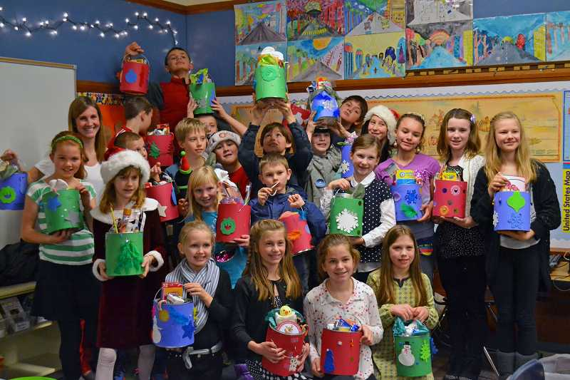 by: SUBMITTED PHOTO - Forest Hills fifth-grade teacher Katherine Cohns students hold their gift buckets high.
