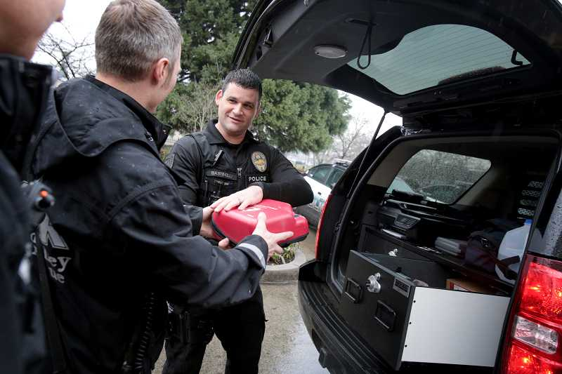 by: TIMES PHOTO: JONATHAN HOUSE - Beaverton Police Department's Officer Tony Bastinelli receives a donated automated external defibrillator unit from Tualatin Valley Fire & Rescue officials.