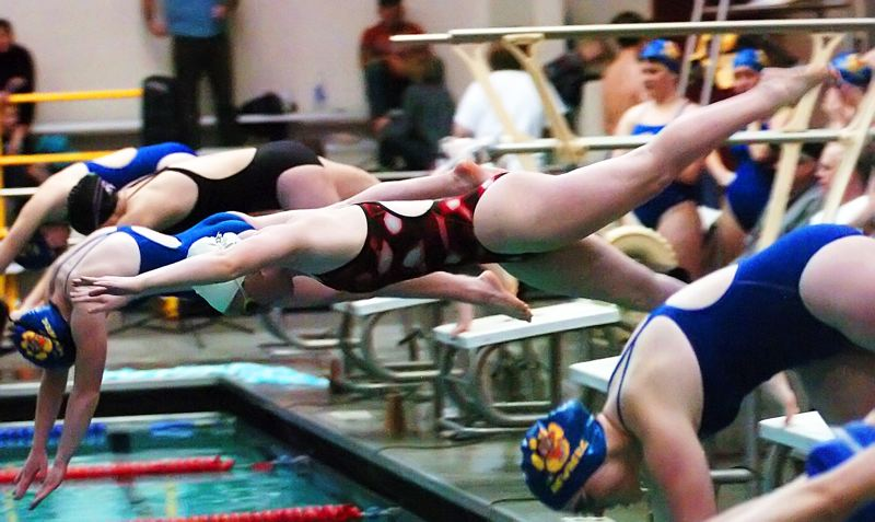 by: DAN BROOD - DIVING IN -- Tualatin High School sophomore Zoe Linford gets off to a flying start in the 200 freestyle relay during Tuesday's meet.
