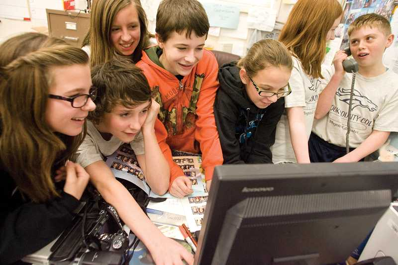 by: KEVIN SPERL - Shelby Reed, left, Brandon White, Rebecca Reed, Noah Chaney, Olivia Cooper, Casey Tunison and Hazel Hoffman work in Jim Crouch's seventh-grade yearbook class, that has expanded to include social media, newsletters and photography.