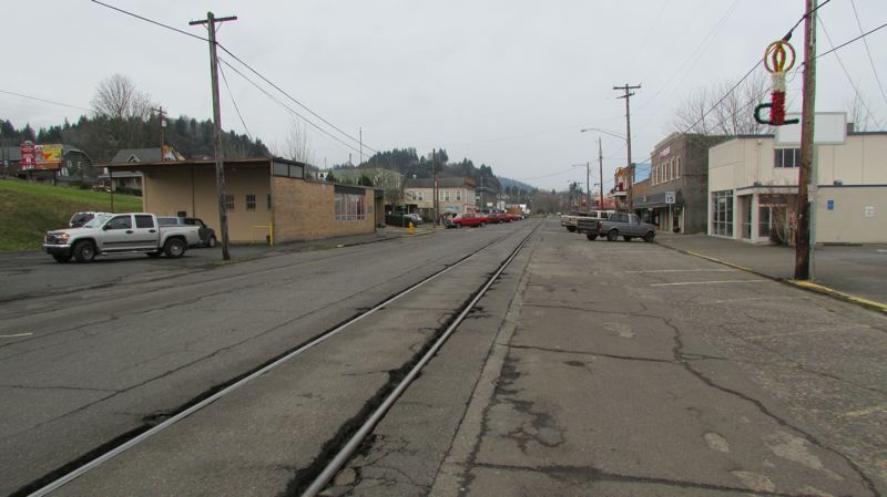 by: SPOTLIGHT PHOTO: MARK MILLER - Railroad tracks cut through the asphalt along A Street in downtown Rainier, arguably the most dangerous rail crossing on the Portland and Western line.