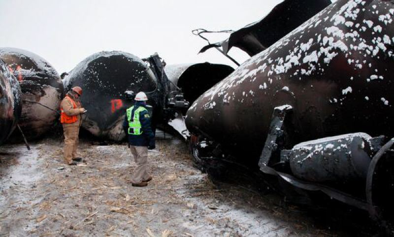 by: COURTESY NATIONAL TRANSPORTATION SAFETY BOARD  - NTSB Board Member Robert Sumwalt views damaged rail cars on scene of BNSF train accident in Casselton, N.D.