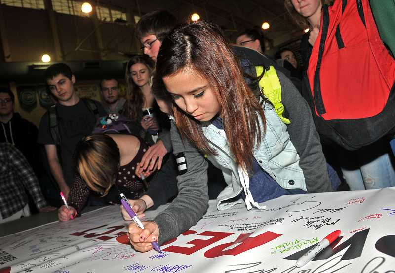 by: PAMPLIN MEDIA GROUP: VERN UYETAKE - Emilia Escobedo, a freshman, signs a banner and pledges to show respect.