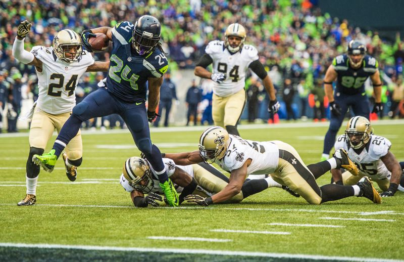 by: COURTESY OF MICHAEL WORKMAN - Seattle's Marshawn Lynch shreds the New Orleans middle defense en route to his first of two touchdowns in last week's NFL playoff victory at CenturyLink Field.