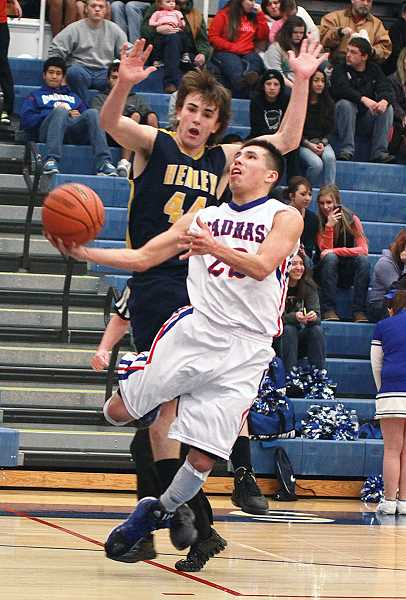 by: BILLY GATES/THE PIONEER - Madras point guard Jared Pichette tries to lay the ball up past a Henley defender during Saturday's game at the Buffalo Dome.