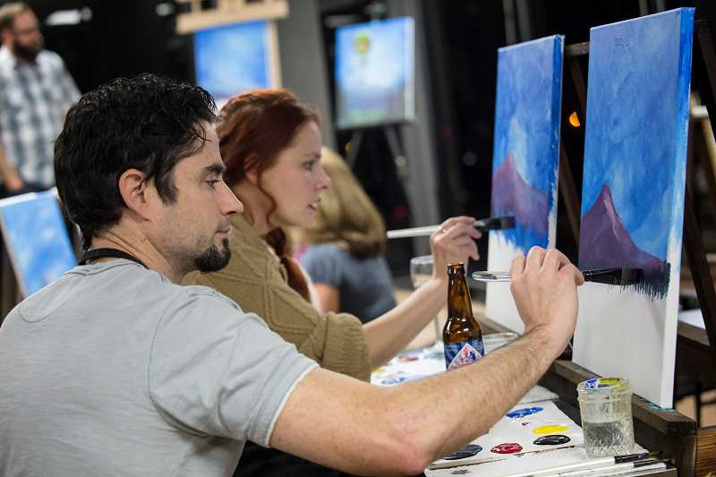 by: TIMES PHOTO: JONATHAN HOUSE - Casey Stewart adds a few touches to the treeline of his painting during a class at Vine Gogh Artist Bar in Tigard.
