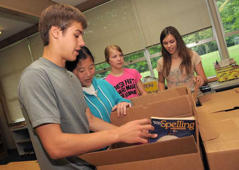 by: REVIEW FILE PHOTO - Former Uplands Elementary School students, from left, John Olsen, 11th grade, Anna Hicks, eighth grade, Kaity Olsen, eighth grade, and Annie Rodgers, seventh grade, help pack up their classrooms in June 2012.