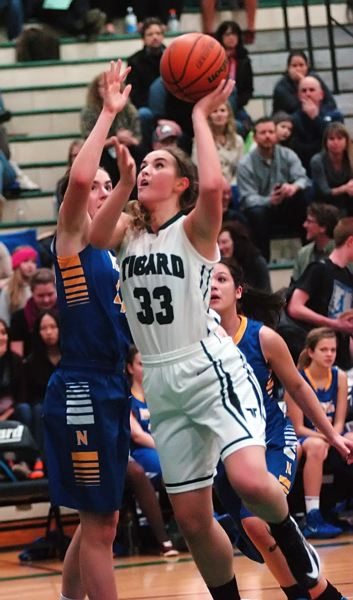 by: DAN BROOD - POWER MOVE -- Tigard senior Stephanie King powers her way up to the basket during the Tigers' win over Newberg.