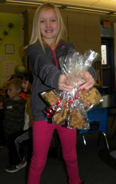 by: TIDINGS PHOTO: KATE HOOTS - Second-grader Jillian Colarchik purchased bags of dog biscuits as gifts for her relatives and their pets.