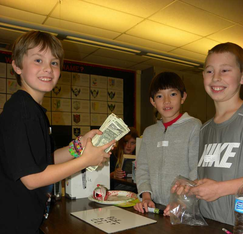 by: TIDINGS PHOTO: KATE HOOTS - From left, Kyle Jensen, Thomas Pierce and Ty Lorenz count money and tally sales Dec. 19. The fourth-graders will donate all the money to the American Cancer Society.