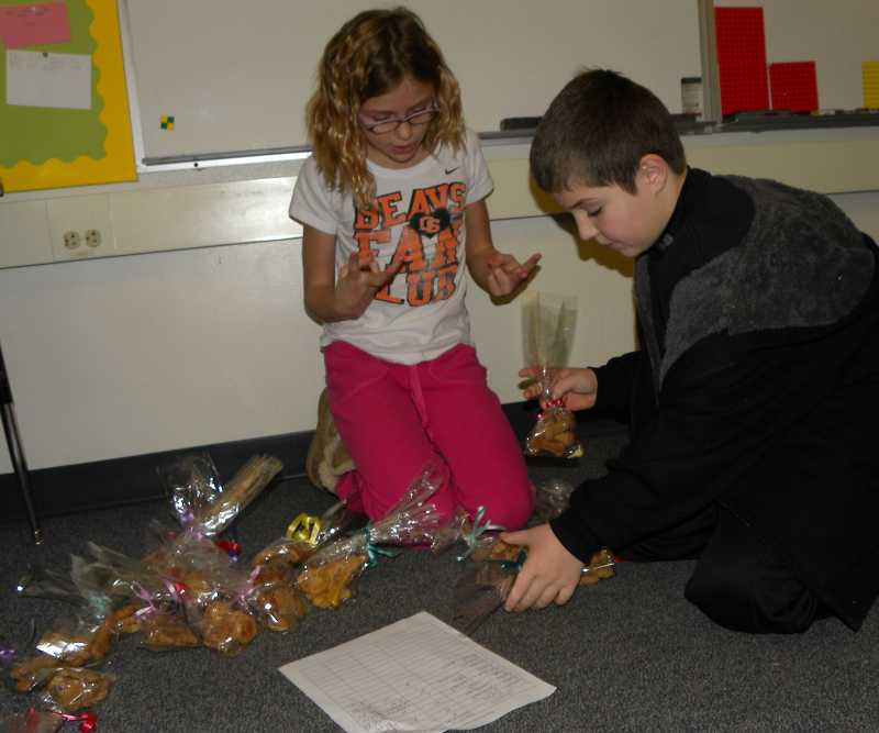 by: TIDINGS PHOTO: KATE HOOTS - Rayna Reynolds and Max Paul sort orders of homemade dog biscuits.