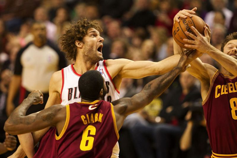 Blazers center Robin Lopez reaches for a rebound against Cavaliers shooting guard Matthew Dellavedova.