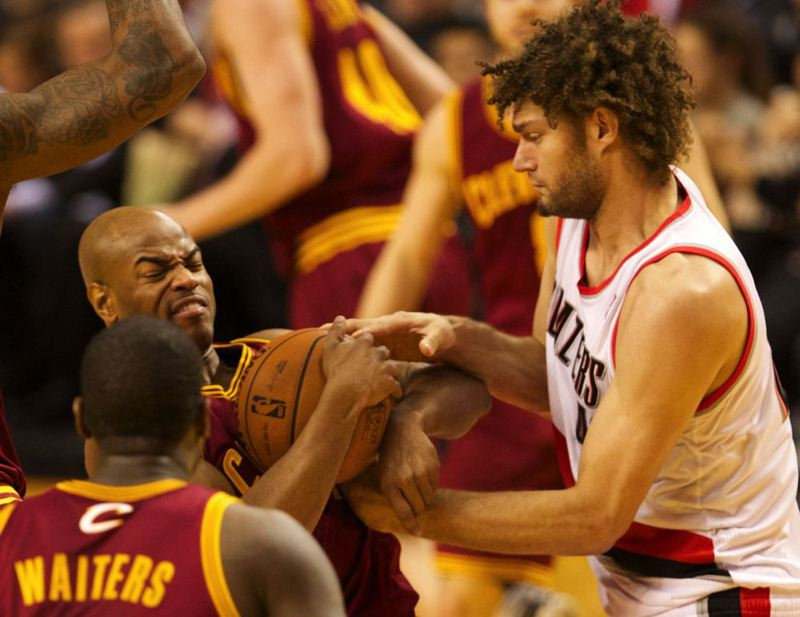Cleveland's Jarrett Jack and Portland's Robin Lopez try to get control of the ball.