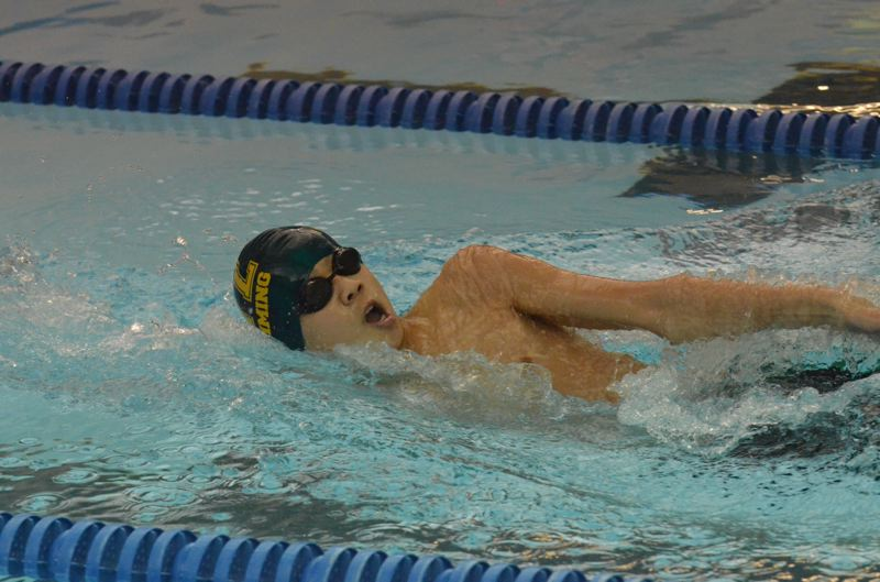 by: JEFF GOODMAN - West Linn's Kyle Vu takes a breath during the 100 backstroke in last week's meet against Canby. Vu won both the 200 freestyle and the backstroke for the Lions.