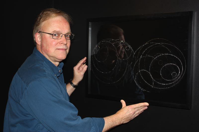 by: HILLSBORO TRIBUNE PHOTO: DOUG BURKHARDT - Artist James Minden displays Convex/Concave, one of his unique 3-D light drawings being featured at the Washington County Museum.