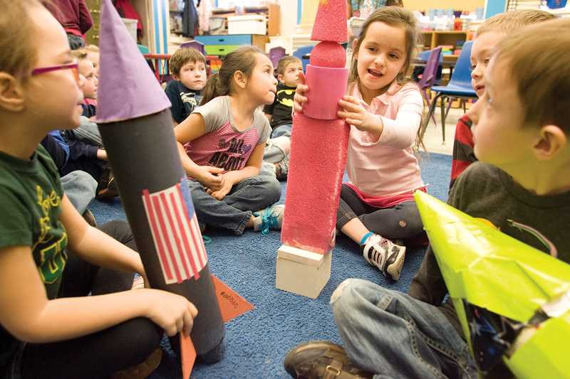 by: KEVIN SPERL - Madison Railey, far left, watches Katelyn Towns, center, assemble her rocket in Karen Bryant's Kindergarten class last Friday. The rockets were used to demonstrate various geometric shapes.
