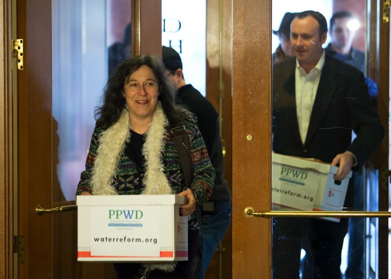 by: TRIBUNE PHOTO BY JONATHAN HOUSE - Floy Jones and Kent Craford deliver 50,213 signatures in support of the Portland Public water District to City Hall on Tuesday. They need around 30,000 valid ones for the meaure to make it on the May Primary Election ballot.