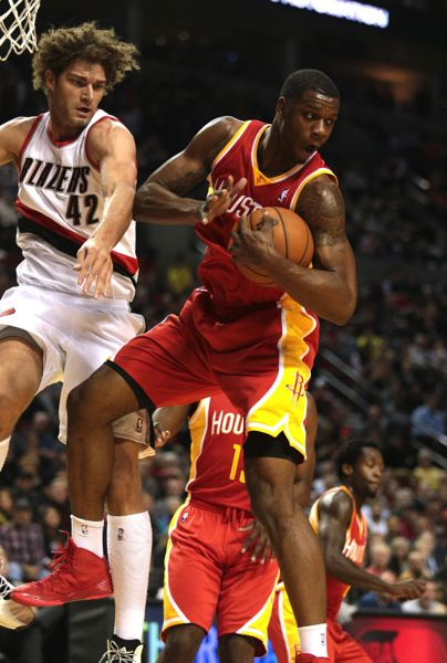 by: TRIBUNE PHOTO: JONATHAN HOUSE - Terrence Jones (right) grabs a rebound for the Houston Rockets in a game against Robin Lopez and the Trail Blazers.