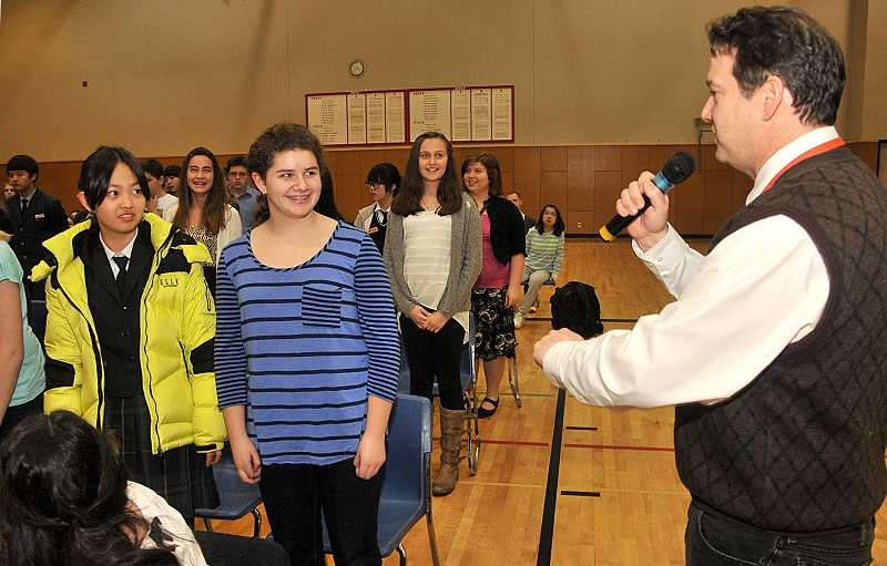 by: TIDINGS PHOTO: VERN UYETAKE - During a welcome ceremoney, Athey teacher John Moshofsky introduces seventh-grader Gabi Fustolo, who is hosting Ryu Ji, an exchange student from the Republic of Korea.