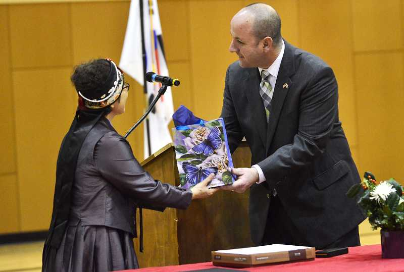 by: TIDINGS PHOTO: VERN UYETAKE - Athey Creek Principal Joel Sebastian gives a welcoming gift to his Korean counterpart, Wi-ja Ryu.
