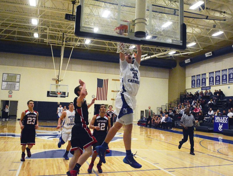by: TIMES PHOTO: MATT SINGLEDECKER - Valley Catholic post Gabe Taylor throws down a two-handed jam in the third quarter of the Valiants' win over Clatskanie on Friday.