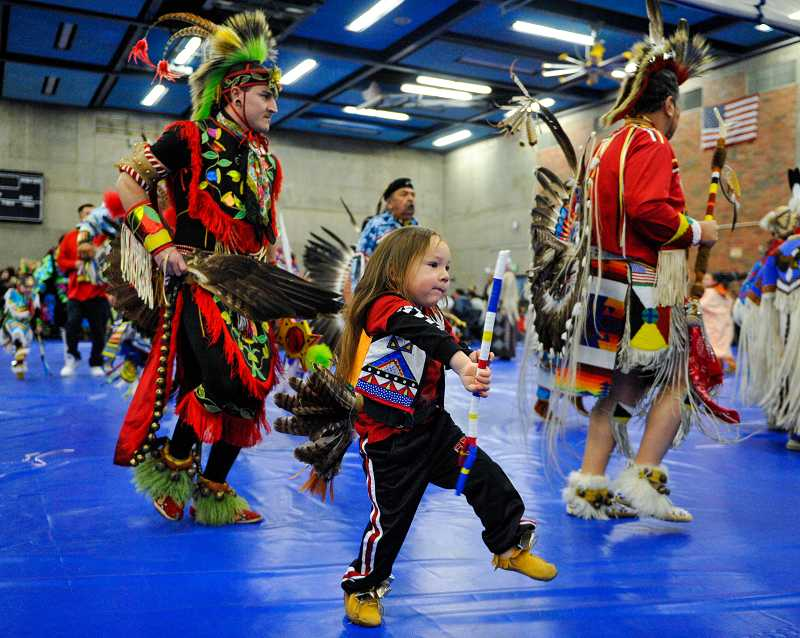 by: TIMES PHOTO: JOHN LARIVIERE - Three-year-old Kingston Black Owl, a Lakota Native American, dances with elder men during the Portland Community College Wacipi Winter Powwow on Saturday at the Sylvania Campus.