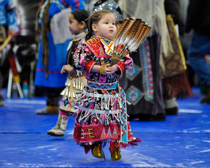 by: TIMES PHOTO: JOHN LARIVIERE - Two-year-old Sweet Song Spotted Eagle, a Blackfeet Cowitchan Tsaout Native American, dances with women and other girls during the Winter Powwow.